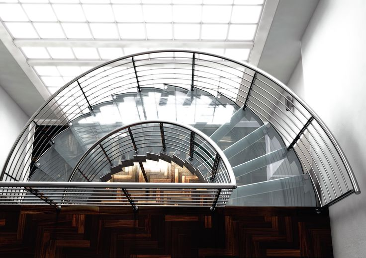 Escalera helicoidal con peldaños de cristal y estructura en acero inoxidable