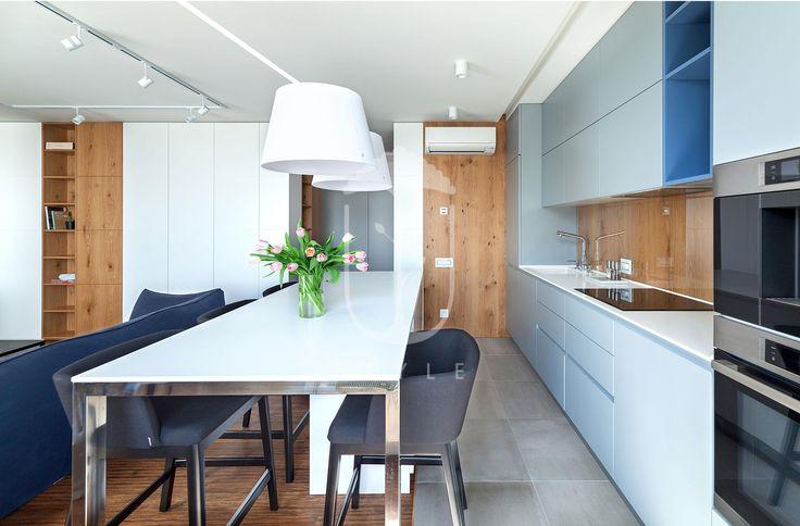 Обеденный стол имеет полубарную высоту. Этот прием помог автору проекта организовать дополнительную рабочую поверхность на кухне.