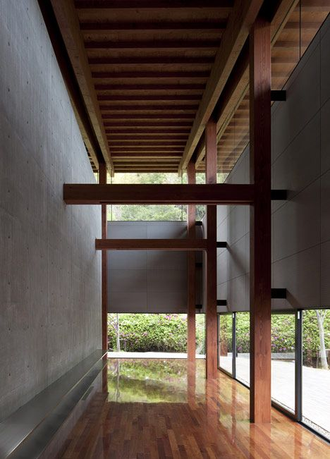 Plain concrete walls + wood columns and beams + tall clerestory windows +wood floor +light and shadow balance Harmonie Hall / Takenaka Corporation