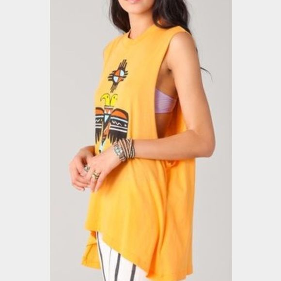 wildfox oversized muscle tee oversized wildfox muscle tee. it is an orange color, but not too bright, with an Aztec bird print. the design has black, orange, yellow, white, and turquoise. as shown in the first picture, the arm holes are kind of low so you might need a shirt or bandeau under it. the front is slightly shorter than the back, which looks cool. can fit larger than an XS because it's oversized. good condition and super comfy. last picture shows Kylie Jenner wearing the same shape…