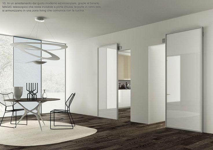 In un arredamento dal gusto moderno ed essenziale, grazie al binario MAGIC telescopico che resta invisibile a porta chiusa, le porte in vetro ben si armonizzano in una zona living che comunica con la cucina. By ZEMMA