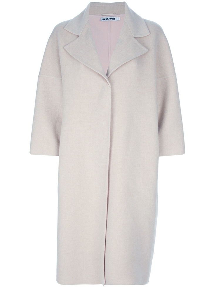 Nude wool oversize coat from Jil Sander featuring a notched lapel, a concealed front fastening, wide three-quarter length sleeves, and a central back seam detail.