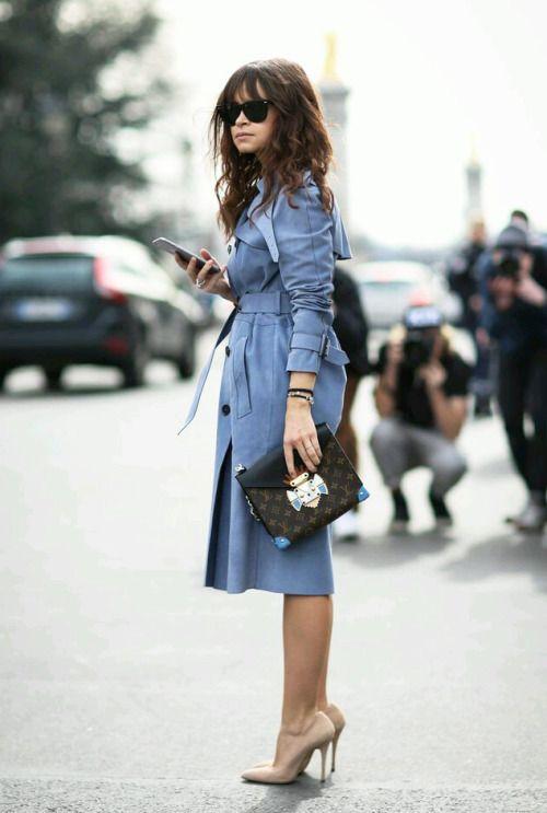 Fashion week street style fashion: Miroslava Duma in royal blue trench coat holding Louis Vuitton clutch bag + nude pumps.