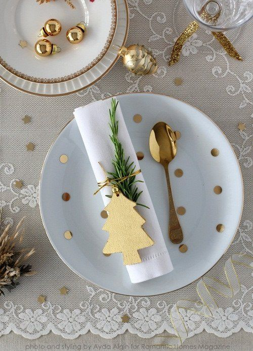 Lovely and delicate Christmas table setting with lace tablecloth and gold tableware