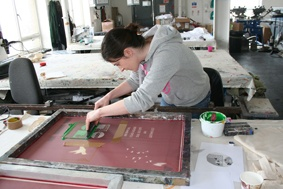 Maeve screen printing - A paddle is pulled across the screen, the ink is forced through the wholes in the screen which makes the design/ logo, as a result the ink is applied to the product in the design required.