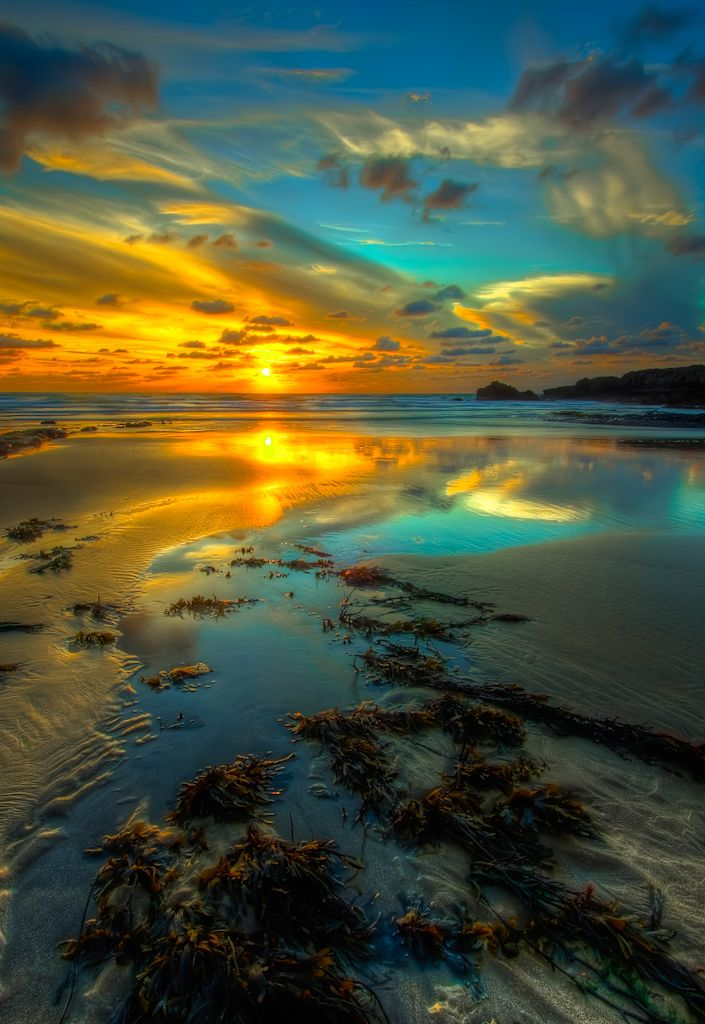 Sunset and calm seas by the breakwater in Bude Cornwall, England