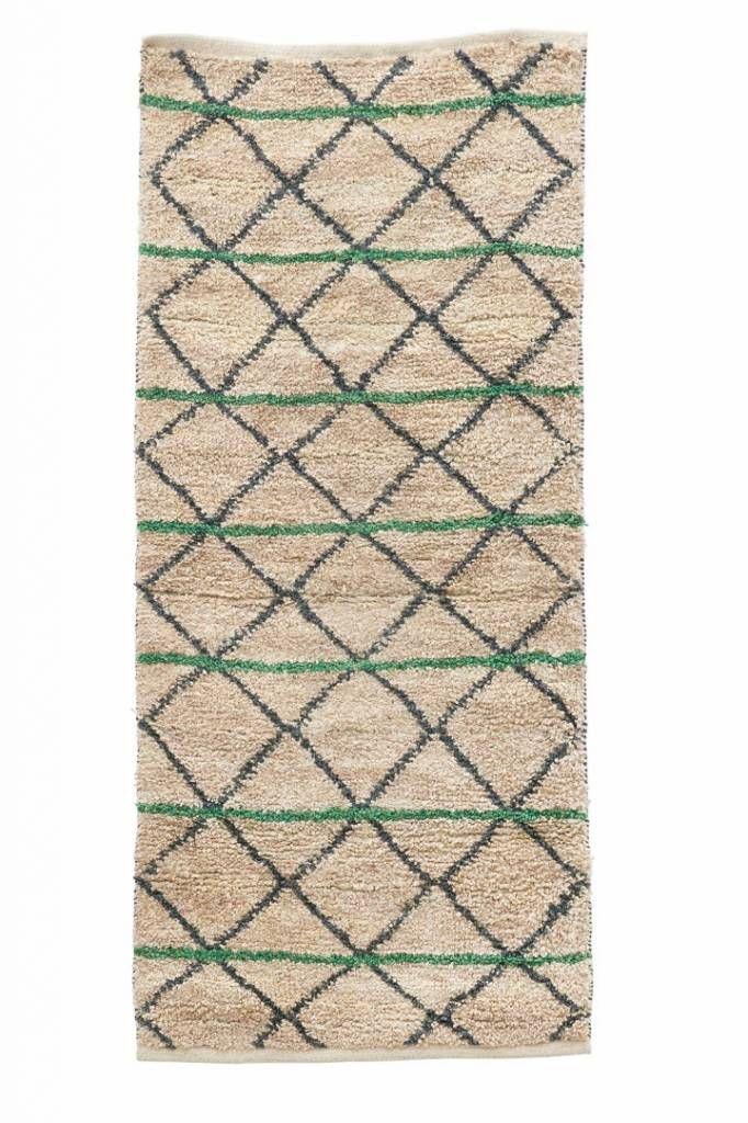 Dit vloerkleed is beige van kleur en heeft groen en zwarte geometrische figuren…