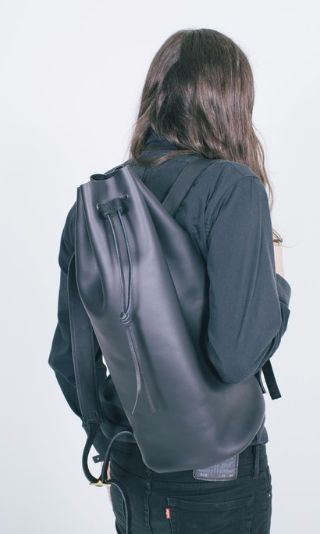 """Made to withstand the elements, this bucket backpack is hand cut from durable .5oz Kodiak leather and finished with hand-painted edges and a drawstring closure. Dimensions: 20"""" x 10"""" x 6"""". 5"""" of adjus"""