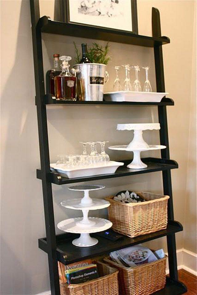 Estante tipo escalera negro de cinco repisas con canastos de mimbre, bandejas para exponer cupcakes, cubeta para el hielo, botellas de licor, bandejas con copas.