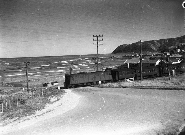 A passenger train passing through a railway crossing at Plimmerton, ca 1930