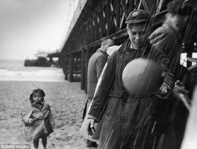 """Vintage children rubber rainwear - Great Britain - 1954 - Single texture rubber lined cotton hooded rain cape - Photo by Joseph McKeown: """"What a summer"""", Holidaymakers at Bournemouth Pier shelter from torrential rain on a wet summer day - Picture Post/Hulton Archive - © Getty Images"""