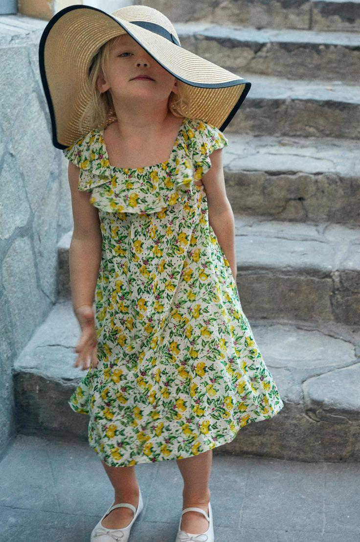 Klänning designade i samarbete med Sofi och Frida Fahrman. Av vävd viskoscrepe. Utställd modell med fin hålspets och tryckt mönster. Vid halsringning som har smal, infälld resår och påsydd volang runt om. Flätat avtagbart knytskärp i midjan.