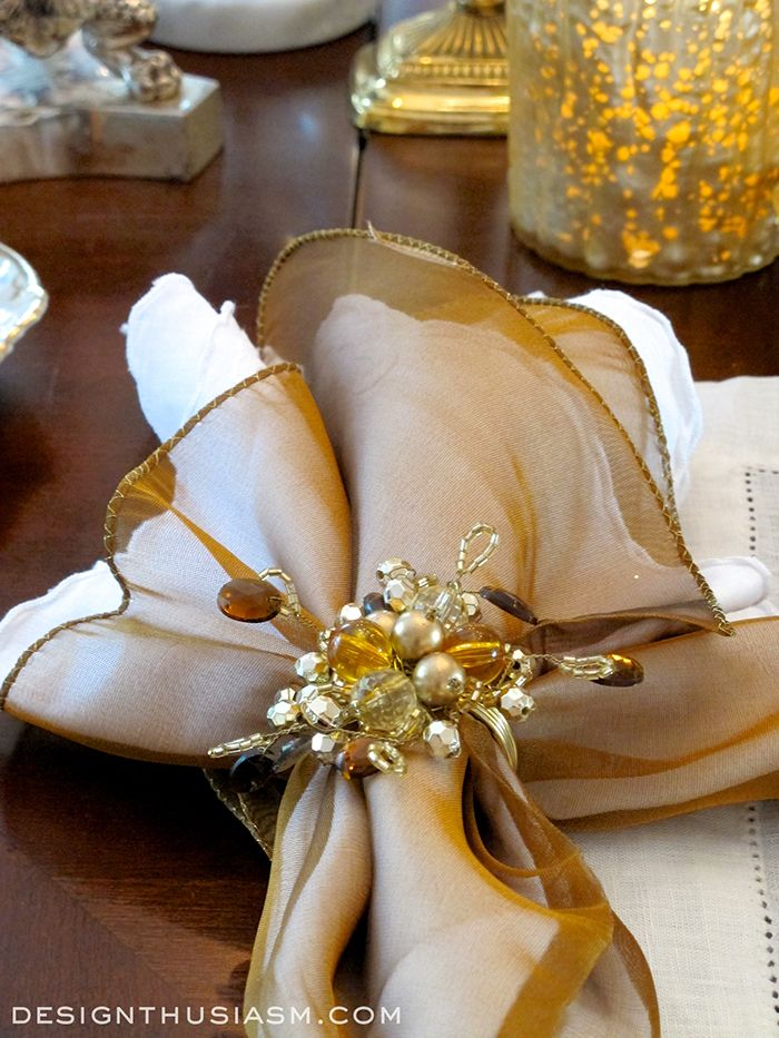 Embroidered white linen layered under bronze sheers, with beaded rings in the amber tones