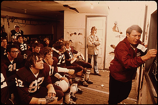 PREGAME DISCUSSION BY THE COACH FOR CATHEDRAL SENIOR HIGH SCHOOL FOOTBALL PLAYERS PRIOR TO A GAME AT JOHNSON PARK IN NEW ULM MINNESOTA. PHYSICAL FITNESS IS STRESSED IN THIS COMMUNITY OF GERMAN DESCENDANTS. THE TOWN HAS A TURNER CLUB FOR YOUTH INTERESTED IN GYMNASTICS. TURNVEREINS OR TURNER CLUBS, BEGAN IN GERMANY IN THE 1800'S AND STRESS HEALTH THROUGH EXERCISE, PARTICULARLY GYMNASTICS THE CLUB CLAIMS TO BE ONE OF THE CO-FOUNDERS OF NEW ULM, 10/1974 (National Archives, RG 412, ARC 558204)