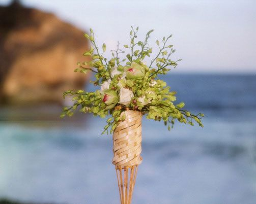 Beach Wedding  Bamboo Tiki Torch « Bollea – Floral Design Gallery Bamboo Tiki Torch adorned with Dendrobium Orchids, Cymbidium and Vendella Roses. Created by MartinRoberts Design.