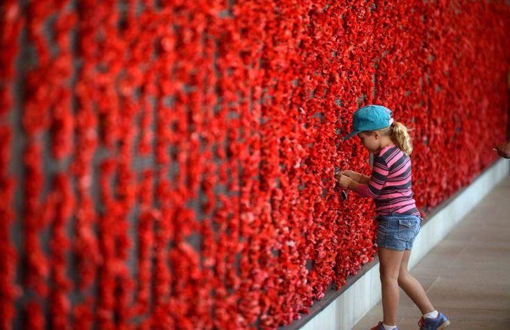 """Una niña deja una amapola en el Memorial de Guerra Australiano durante la conmemoración del """"Día del Recuerdo"""" por los soldados caídos en combate desde la Primera Guerra Mundial."""