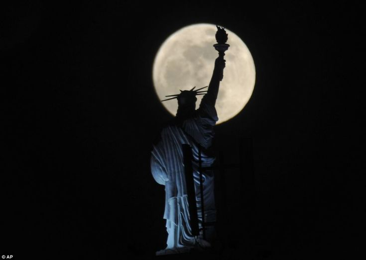 *The full moon provides a stunning backdrop for Kosovo's answer to New York's Statue of Liberty on top a hotel in the capital Pristina this evening, May, 2012