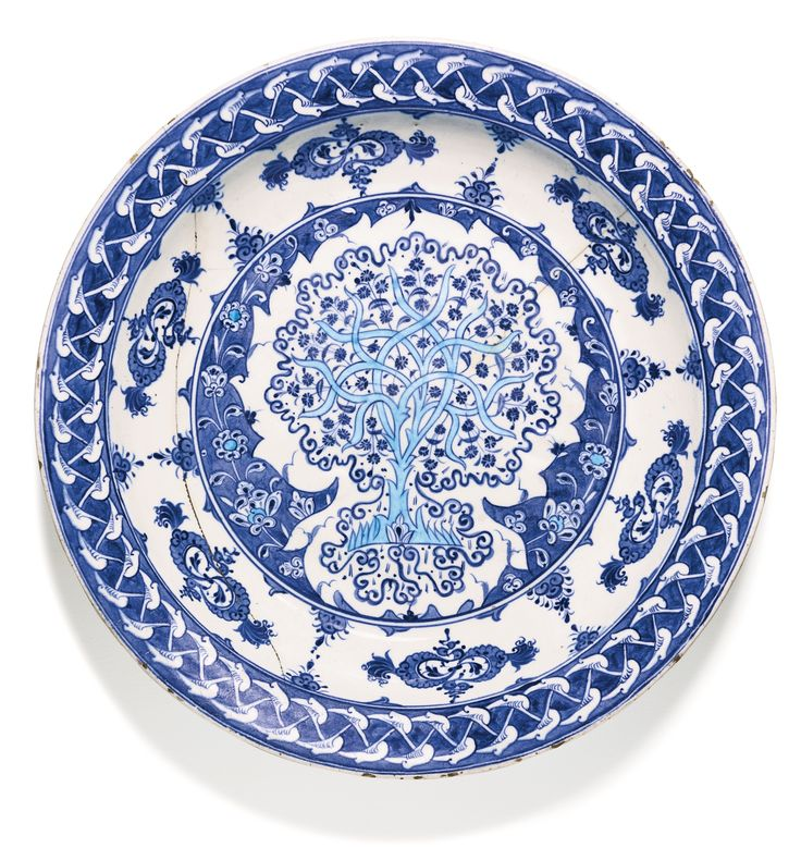 """AN EXCEPTIONAL IZNIK BLUE AND WHITE POTTERY DISH, TURKEY, CIRCA 1520 the deep round dish with everted rim painted in underglaze cobalt blue and turquoise on a white ground, the central medallion featuring a tree issuing finely drawn floral blossoms, within a tight scroll border, with lotus-blossom stems, the cavetto with cloud scrolls, the rim with a rumi-arabesque pattern reserved against a cobalt-blue ground, 35.5cm. diam. Sotheby""""s"""