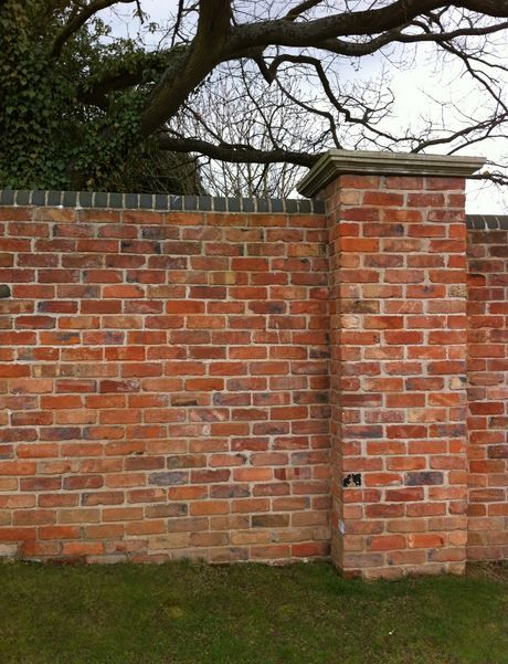 Walled garden - brick wall with piers shown here with blue/blackbrick coping to top of wall and a stone pier cap