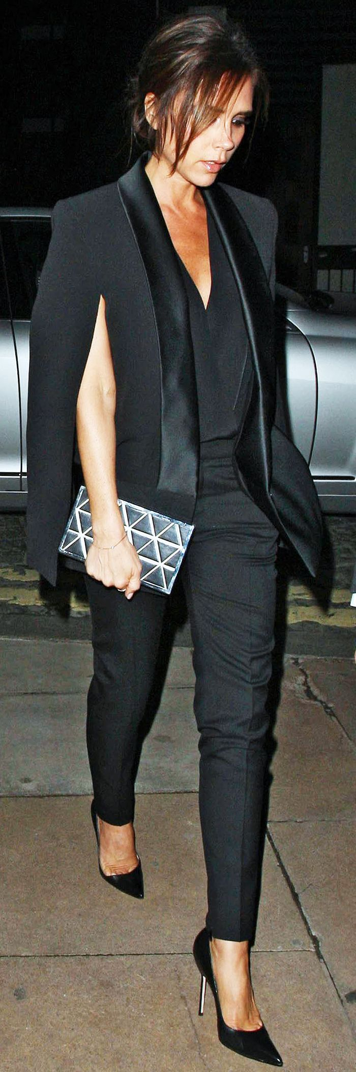 Victoria Beckham in a tuxedo cape, trousers, and point-toe heels