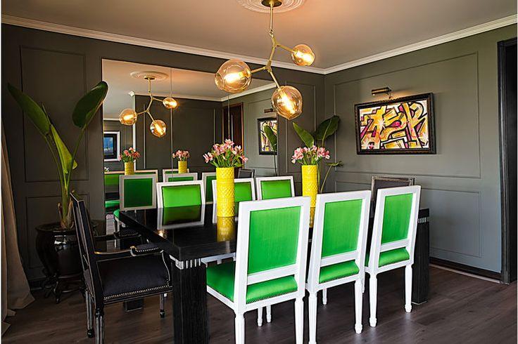 Sillas de estilo neoclásico de seda color verde. Mesa y sitiales negros. Muros verde olivo, sobre uno de los cuales colgamos un cuadro de graffiti y en el otro un gran espejo. Lámpara de bronce, colgante, de tulipas. Maceteros pekin negros con strelitzia.