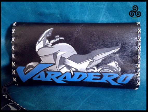 VARADERO: Tobacco pouch with the Honda Varadero logo on it, in genuine black leather ... The logos are burnt with a pyrographer and painted with special colours for leather. Inside there are pockets for filters and papers, and closes with magnetic buttons. It comes with a little case for the lighter Dimensions: 150mm x 200mm.