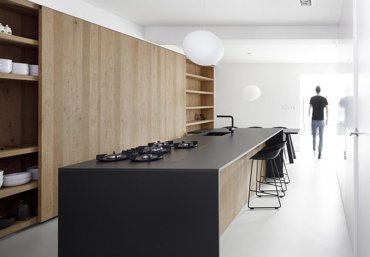 A Foscarini Gregg Pendant hangs above the kitchen table. The island is made of oak with a thin, black stone countertop.  Courtesy of Ewout Huibers.