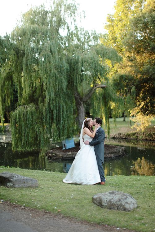 Romantic image of married couple kissing by the pond.