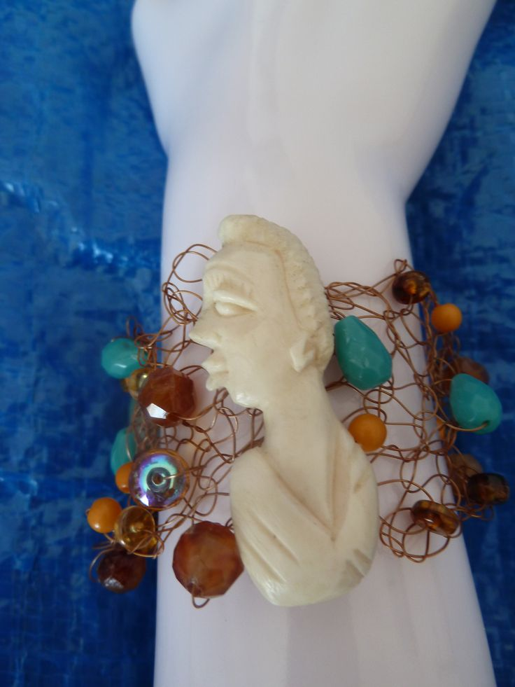 The is the only one I found like this in the UK a couple of years ago. The centre piece looks like bone and is a craved African Woman's head.  This beautiful Vintage piece has copper colours coated wire with woven glass and crystal beads in the colours of teals, browns and coppers tones.40mm wide. A fun piece to wear to the beach and/or evening.www.etsy.com/your/shops/suemacdougallfineart/tools/listings/229972267