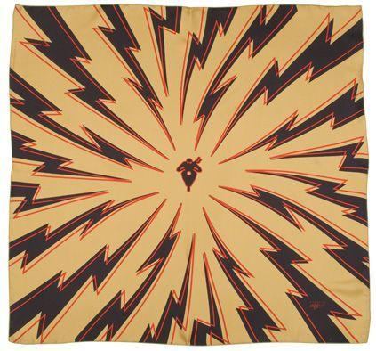 Šátek ze 100% hedvábí o velikosti 70 x 70 cm. Na zlatém podkladě jsou výrazné černé blesky a veprostřed silueta motorkáře. Výrobce: A Piece of Chic, Lyon, Francie