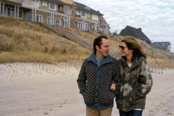 American author and political activist Gloria Steinem walks on the beach, arm in arm with Canadian-born businessman Mortimer Zuckerman, New York, January 1, 1984.
