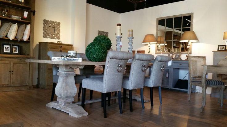 Mebli do jadalni w postaci prostokątnego stołu na masywnych nogach i kompletu krzeseł tapicerowanych z ozdobnymi uchwytami na oparciach. Całość kompletu do jadalni utrzymana w szarym kolorze.