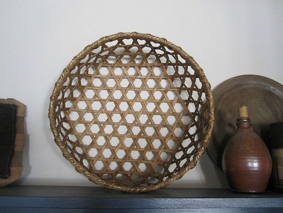 This medium sized version of the Shaker Cheese Basket is a reproduction that I have woven from reed. Historically, this type basket was used by the Shaker people when they made cheese. Basically, the basket was a strainer used with cheesecloth to separate the curds and whey. This basket is approximately 15 in diameter and 5 high. Woven in the traditional hexagon weave pattern famous to the Shakers.  Once completed, the basket was stained in my homemade dye of boiled black walnuts. This stain…