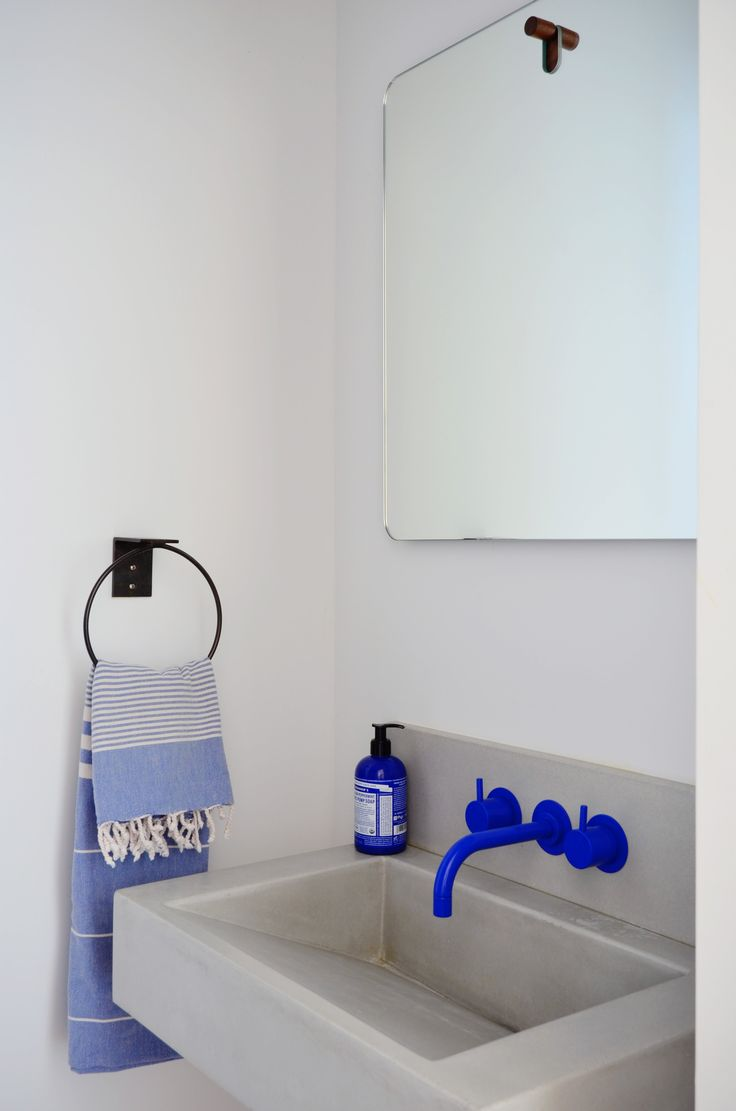 A bright cobalt blue Vola faucet provides a splash of color in the powder room.