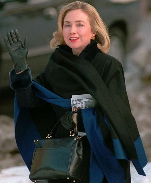 Hillary Rodham Clinton, carrying a copy of her book 'It Takes A Village' departs a Washington radio station on Jan. 15, 1996. | AP Photo
