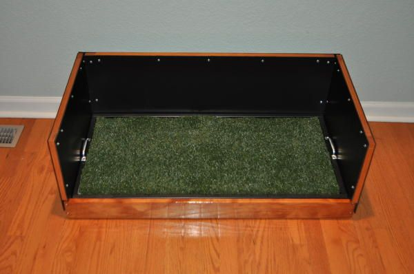 A small male dog litter box that is ideal for indoor usage and has a protective wall around it. This dog potty is for dogs weighing between 10 and 20 lbs
