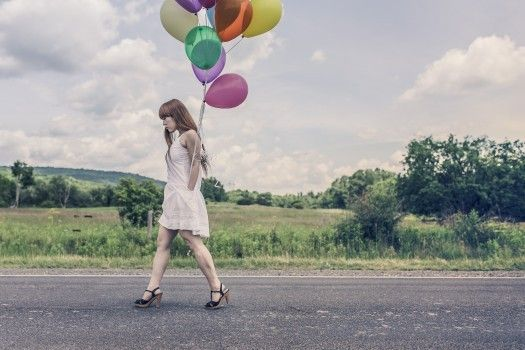 Young woman walking with balloons on asphalt road
