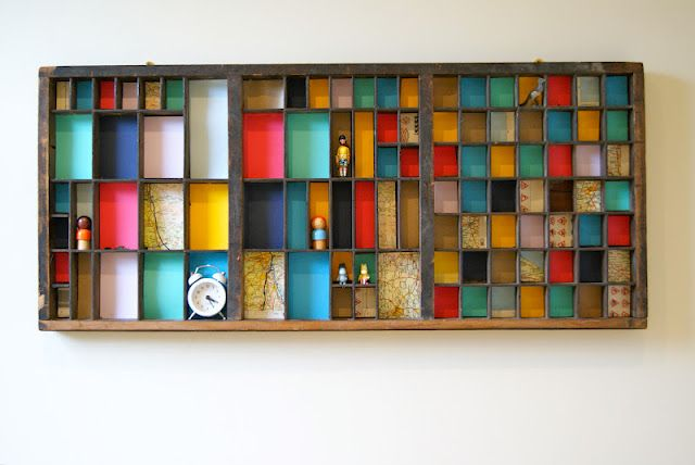 Letter Press Tray mounted on the wall and filled with coloured paper/map pages