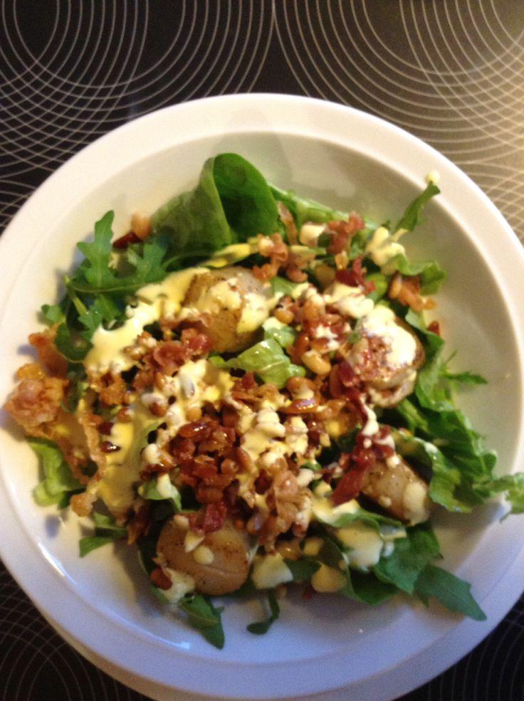 Salade met rucola, sint jacobsmoten, pijnboompitten, olijfolie en mosterddressing