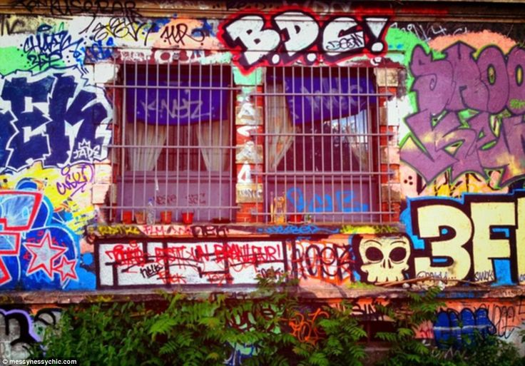 Where the new meets the old: Graffitti sits alongside overgrowth on a building backing onto the railway