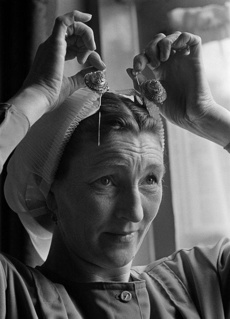 Vrouw in klederdracht zet haar kap op, Scheveningen (1950-1960) Creator: fotograaf: Oorthuys, Cas