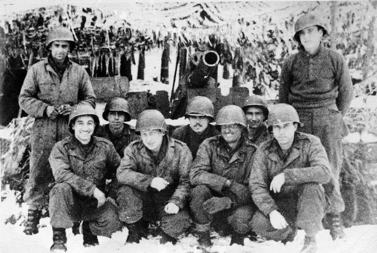 GIs pose with a 105-mm howitzer of the 33rd Field Artillery during the Battle of the Bulge in December 1944.
