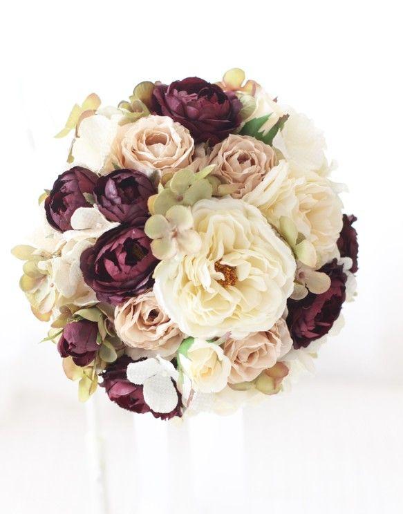 秋〜冬のウェディングにふさわしいブーケ‼︎フリル咲きの大輪のバラと、ダークパープルのバラを使い、しっとりと落ち着いた雰囲気のブーケです。シルクカラーやレッド、ブルーのドレスに合わせやすく花嫁の美しさを一段と引き立てます。めずらしい秋色アジサイを使うことで、個性的でおしゃれさがアップ♪こだわりのウェディングにオススメです。☆アーティフィシャルフラワー(最高級品質の造花)バラ(3種類)、紫陽花(2種類)☆直径約20cm