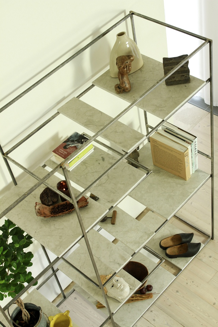 SKID Bookecase. The linearity and the working of the iron meet the naturalness of the marble and together are joined in a materic  binomium that runs to a sober and elegant geometrical strictness.