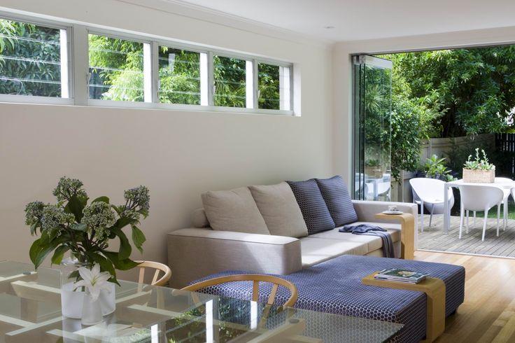 Living area opens up via frameless glass doors to an outdoor entertaining area. Brooke Aitken Design.