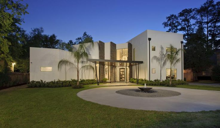 modern Texas home with dark stacked stone accents, large lawn, circular driveway and white exterior