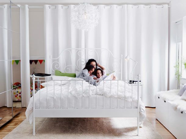 Bedroom picture with white linen and textiles with family on the bed