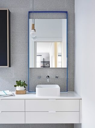 The vibrant blue colour of the front door is continued inside in the ensuite's mirror frame and the paint-drip feature by the stairs.