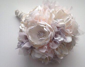 Questo bellissimo bouquet è fatto nei toni del rosa cipria chiaro, pallido rosa, champagne e avorio. I fiori sono fatti tutti di tessuto. Ogni fiore è rifinito con perle e strass centri. Tessuto di pizzo e filler tra ogni fiore. Centri di fiore e perle variano.  Questo è mostrato in un bouquet di grandi dimensioni che misura circa 8 pollici di larghezza, 25 pollici in giro e contiene 14 fiori.  Disponibili in altre dimensioni. Vedere a discesa Opzioni al check-out per le altre grandezze e…