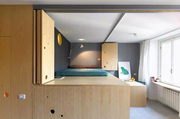 This wooden wall opens up to reveal a lofted bed, a dining room and another window, adding more light to the apartment.